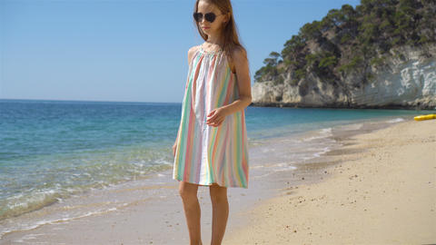 Beautiful little girl in dress at beach having fun. Funny girl enjoy summer Live Action