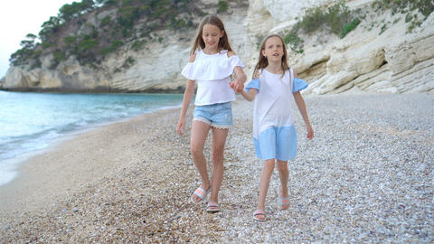 Active little girls at beach having a lot of fun Live Action