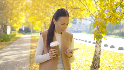 Fall concept - beautiful woman drinking coffee in autumn park under fall foliage Live Action