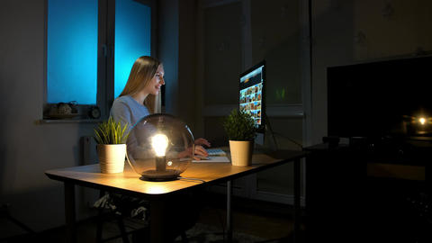 Smiling woman working on computer at night. Smiling female in checkered shirt Live Action