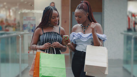 African women with shopping bags are using phone to online shopping Live Action