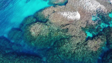 Drone aerial view of the beautiful blue sea that is rich in coral reefs of Ishigaki Island Live Action