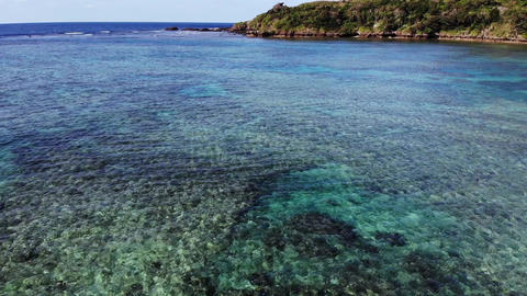 Drone aerial view of the beautiful blue sea that is rich in coral reefs of Ishigaki,Nose in circle Live Action