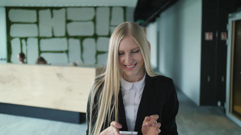 Cheerful young woman with phone in office. Pretty blond woman with long hair Live Action