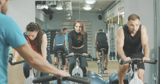 Back view of trainer instructing people on cycling equipment in sports club Live Action