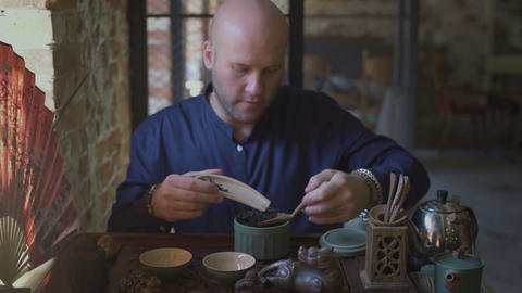 Bolde man doing a traditional chinese tea ceremony Live Action