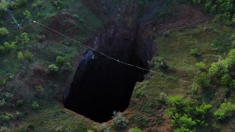 Aerial footage of a massive natural pit with a rope stretched over it, slackline ライブ動画