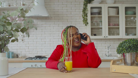 Positive african woman speaking on cellphone at home Live Action