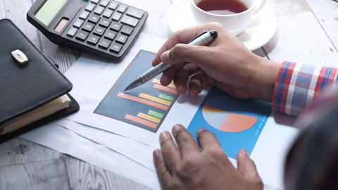 young man hand analyzing financial data at office desk ライブ動画