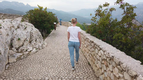 Blonde girl walks on defensive Walls of medieval castle in Europe mountains Live Action