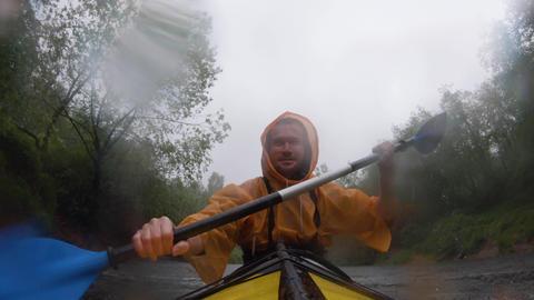 Russia, Kirishi, 25 May 2019: The men in a raincoat of orange color floats on a Acción en vivo