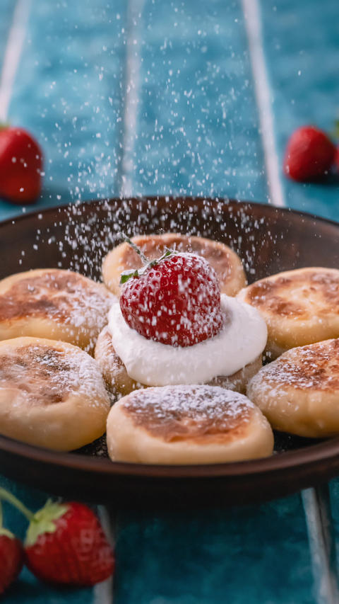 Sprinkling powdered sugar with powdered sugar cottage cheese pancakes, cheesecakes with strawberry. Live Action