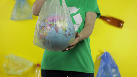 Unrecognizable woman with Earth globe in plastic package. Save ecology. Plastic Live Action