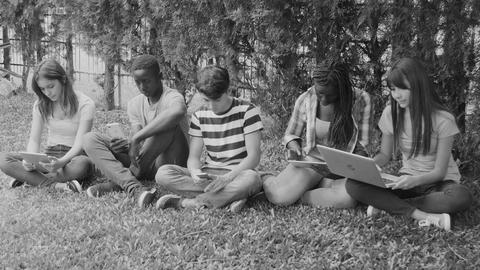 Group of mixed races teenagers seating on the grass playing with techno gadgets Live Action