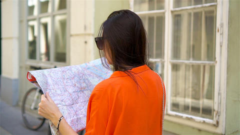 Young woman with a city map in city. Travel tourist girl with map in Vienna Live Action