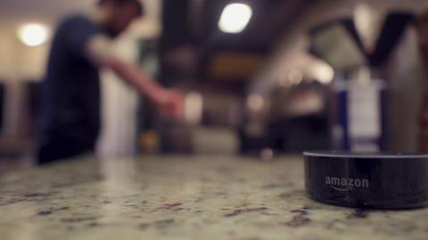 Alexandria, VA, USA - June 2020: Amazon Alexa helping cook in kitchen Live Action