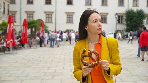 Beautiful young woman holding pretzel and relaxing in park Live Action