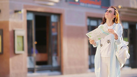 Happy young woman with a city map in Europe. Travel tourist woman with map in Live Action