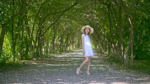 Carefree curly girl in hat twisting on summer blooming alley background. Happy Live Action