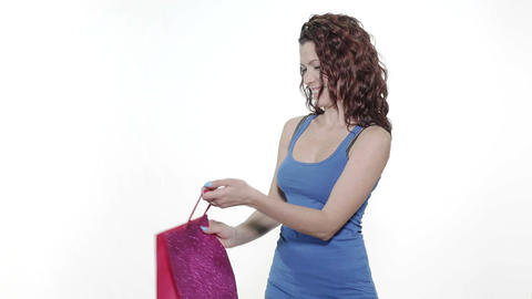 4k - Young attractive woman is offered a gift bag and looks curiously in it Footage