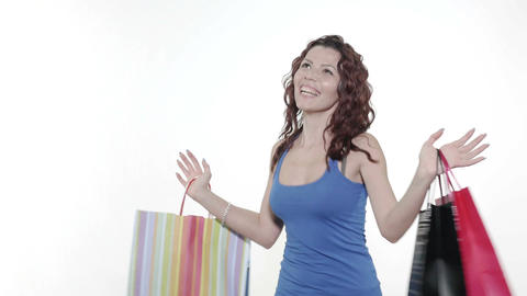 4k - Young attractive woman spins and dances while holding shopping bags Footage