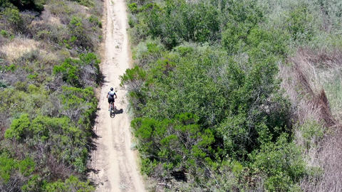 Aerial view of riding mountain bike in a small singletrack trail in the mountain Live Action