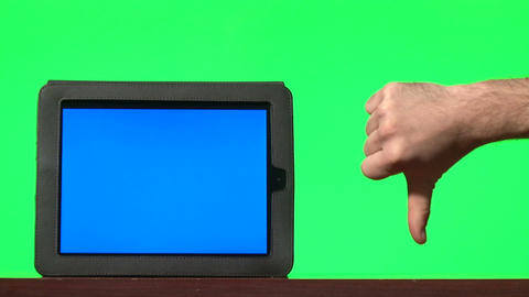 Man presenting digital tablet with a blue screen and gesturing: thumbs up, disli Footage
