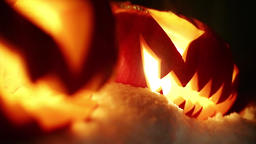 Halloween pumpkins in the winter snowy night with overflying ghost. Looped Footage