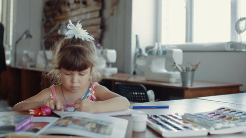Little pretty girl in draws with colored markers at table in room Live Action