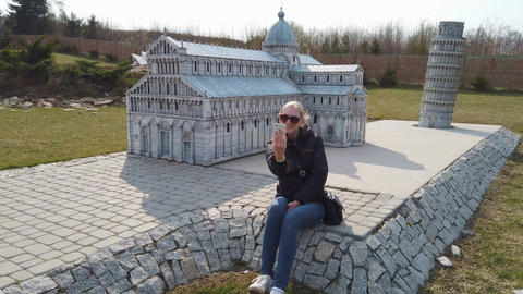 Woman takes a selfie near a miniature model of the old Cathedral, Europe. Park Live Action
