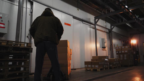 mover adjusts hydraulic hand of truck with boxes in workshop Live Action