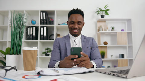 Front view of cheerful good-looking relaxed young black -skinned male office Live Action