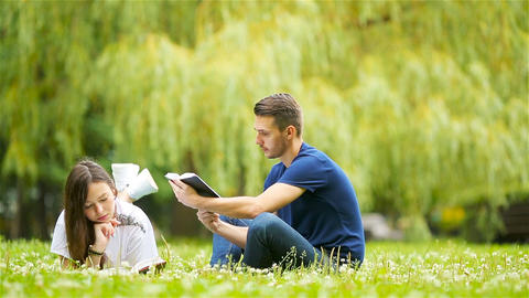 Relaxed young couple reading books while lying on grass Live Action