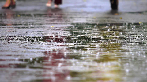 There is heavy rain and puddles on the background to run a human foot Live Action