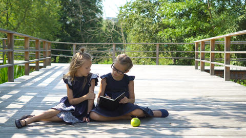Adorable little school girls with notes and pencils outdoor. Back to school Live Action