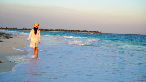 Beautiful woman on summer holidays on white beach. Happy girl walking in summer Live Action