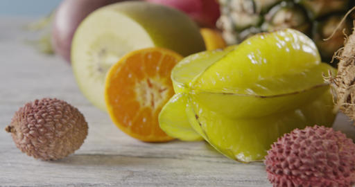 Close-up dolly slow motion of passion fruit, carambola, litchi on a wooden Live Action