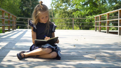 Adorable little school girl with notes and pencils outdoor. Back to school Live Action