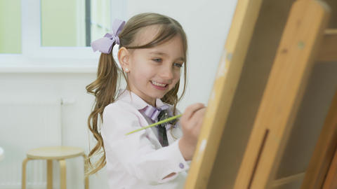 little girl paints a picture and looks at the camera. Happy little girl smiling Live Action
