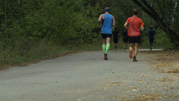 two male runners run in autumn city Park Filmmaterial