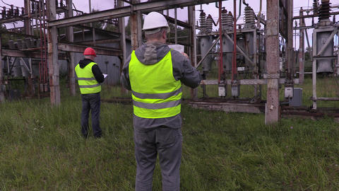 Electrician engineer check out blueprint in substation Live Action