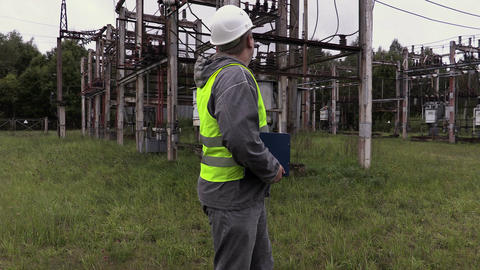 Electrician engineer talking on the phone at substation Live Action