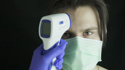 Health-care worker, doctor checks man's temperature Live Action