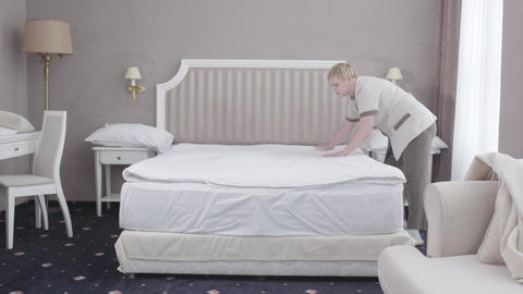 Adult Caucasian maid making bed in hotel room. Wide shot of professional female Live Action