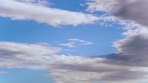 4K uhd sky timelapse with strange white and grey clouds formations in blue sky Live Action