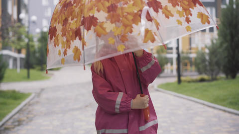 Cheerful little Caucasian girl spinning umbrella outdoors. Portrait of smiling Live Action