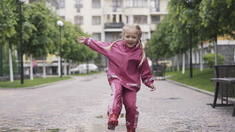 Portrait of joyful little girl having fun playing in puddle on rainy day. Wide Live Action