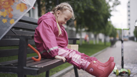 Cute joyful Caucasian girl sitting on bench on rainy day and shaking legs. Side Live Action