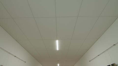 Camera movement and look up, white ceiling with lighting. POV Live Action