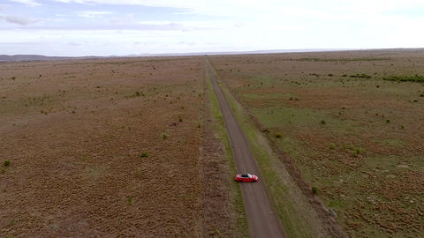 Aerial view of red car reverse and moving on country road Live Action